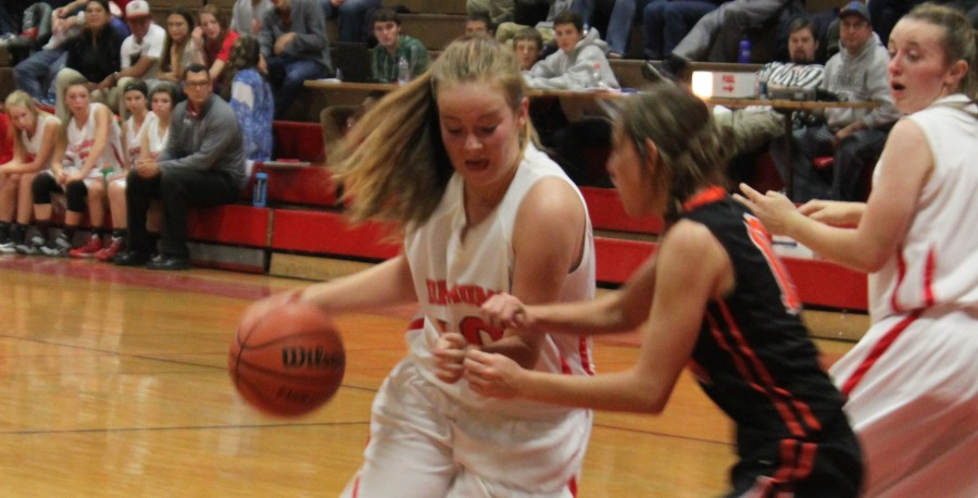 Stephanie Basye drives to the basket with Katrina Chandler trying to get open.