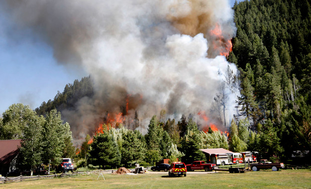 A structure burning on Lightner Creek Road west of Durango, Colo., on Wednesday, June 28, 2017, quickly spread into the surrounding forest, creating the Lightner Creek Fire and burning an estimated 100 acres. (AP Photo/Durango Herald,Jerry McBride)